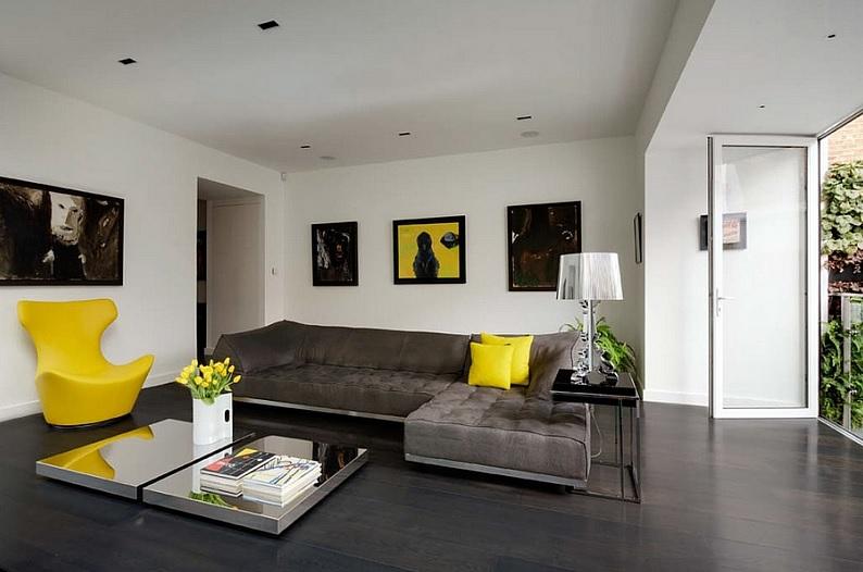 Gri duvar boyalı salonda sarı ve kahverengi eşyaların kombini